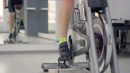 close cropped : Close up of feet of a woman losing weight cycling on indoor bike Stock Footage