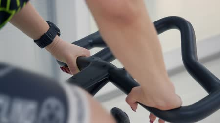 meia idade : Middle aged blonde woman is intensively riding on stationary bike. Hands and drops of sweat on bicycle handlebar, close-up view. Sport concept.