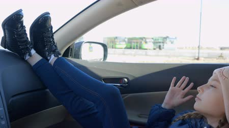 hallgat : Teen girl in winter clothes is listening music sitting in the car. Side view. Stock mozgókép