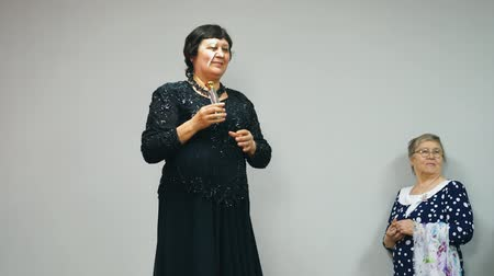 czarne : Elderly fat woman in black dress holds a bottle of perfume presentation of new perfume odore. She sprays perfume on the air for audience. Side view.