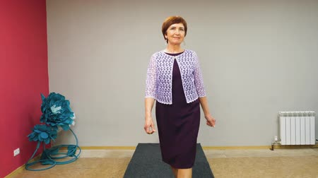 szörnyszülött : Elderly senior woman walks the runway in dress preparing to local fashion show. Defile, front view. Stock mozgókép