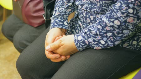 blúz : Elderly woman is sitting in line, waiting and keeping her hands joint on her legs. Hands close-up.