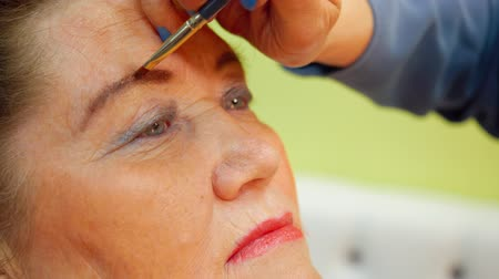 contorno : Face elderly woman while eyebrows makeup in beauty studio close up. Visagiste applying makeup on face mature woman in makeup studio. Beauty and fashion concept