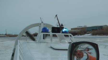 bancário : Small hovercraft on frozen river with working propeller and blue lights.