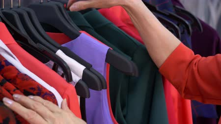 buyer : Hands of elderly woman choosing clothes in fashion shop while shopping. Close up mature woman shopping clothes in stylish shop