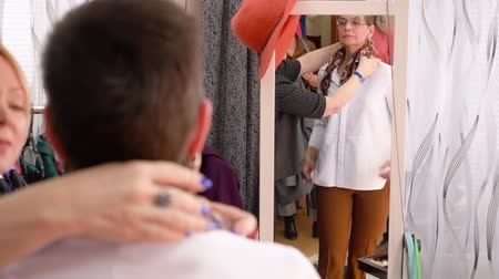 glass master : Middle aged woman stylist puts scarf on the client to complement the image standing in front of the mirror.