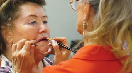 szminka : Elderly woman is painting her friends lips with brush for the party. Close-up portrait.