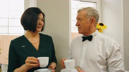 kravata : Elegant senior man and woman on date are drinking tea and talking together standing near the window.