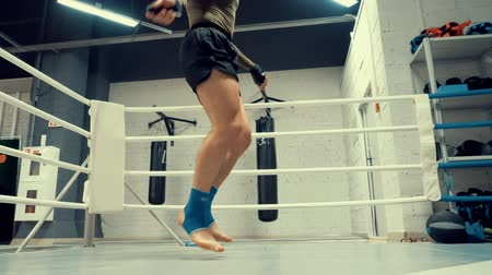 saut a la corde : Boxer Fighter Training Jump on Rope Slowmotion. Strong Athletic Caucasian Man Exercise in Gym. Athlete Legs for Active Lifestyle Motivation. Healthy Sport in Boxing Ring Slow Motion Footage