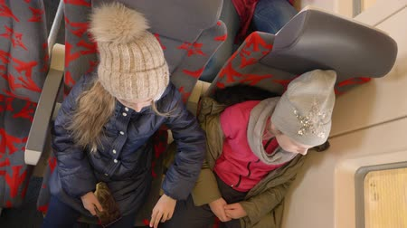 věk : Two girls travel by train. Overhead view two teenage girls looking to the window, while traveling by the train.