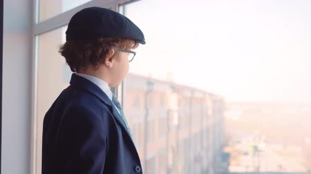 gravata : Little boy in cap, glasses and official suit looking like a businessman is watching at window.