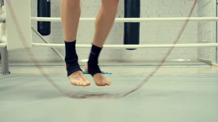 lano : Professional fighter is skipping on jumping rope crossing his legs, feet close-up.