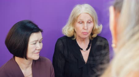 jubilados : Elderly women gossip with each other, discussing their problems on purple background.