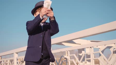 имитация : Little boy looking like a businessman in suit is wasting money, throws money in the air from bridge on the street.