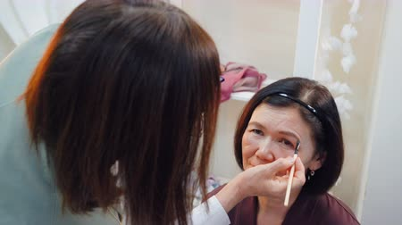 семидесятые годы : Makeup artist doing makeup eyebrows with cosmetic brush to elderly woman. Visagiste shaping and coloring eyebrows of mature woman in beauty studio. Beauty and makeup concept