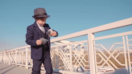 emit : Young business boy in black suit and hat throwing money from bridge. Carefree boy waste money standing on pedestrian bridge. Spending money concept