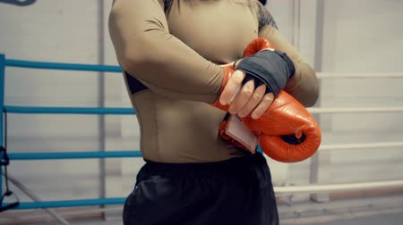 fit : Man boxer putting boxing gloves before fight training on box ring. Young man in red boxing gloves preparing to fight in boxing club. MMA concept