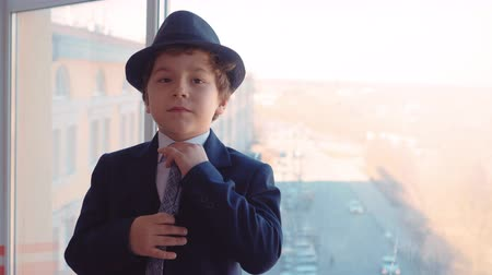 imitace : Portrait young boy in business suit, tie and hat on window background in office. Business boy correcting straightins tie and looking to camera on office window background Dostupné videozáznamy