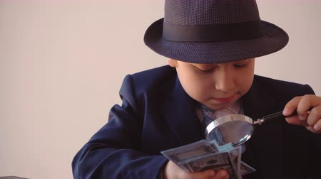 examinar : Portrait of child boy looks like a businessman in hat and suit is looking at dollars with magnifier sitting at table in his office, front view close up
