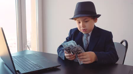 utánzás : Portrait of child boy looks like a businessman in hat and suit in his office sitting at table counting dollars near the laptop, front view.