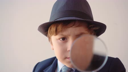 gravata : Portrait of child boy looks like a businessman in hat and suit in his office is looking through magnifier at light background, front view.
