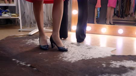 ковер : Three pairs of womens legs in elegant heel shoes in store in front of the mirror, legs close-up.