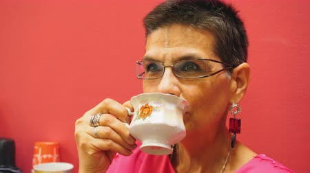 teacup : Beautiful Senior Woman Drinking Tea in White Cup. Elderly Pensioner Enjoying Aromatic Beverage. Aged Retired Female in Glasses. Pensioner with Black Hair Holding Teacup in Hand Close-up Footage