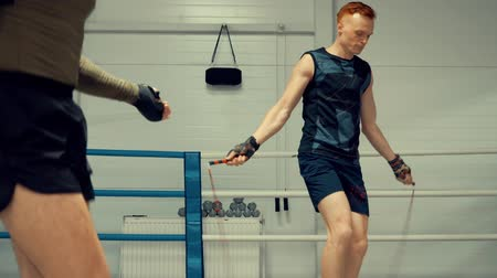 boksör : Two Boxer Skipping on Jumping Rope Slowmotion. Professional Fighter Exercising in Gym on Boxing Ring . Sportsman Training Legs in Sport Club. Strong Workout for Young Caucasian Athlete in Sportwear
