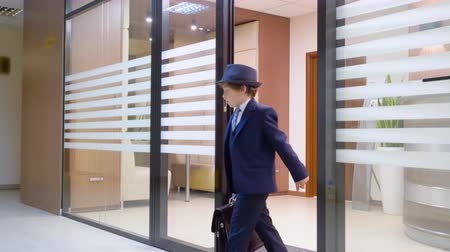 nákrčník : Child boy looks like a businessman in hat and suit with briefcase in hand is leaving his workplace in office. Adults life parody. Business spy look around office secret