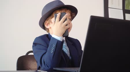 utánzás : Kid boy looks like a boss in suit and hat is speaking mobile phone with client sitting at table near the laptop in his office. Adults life parody. Stock mozgókép