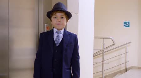 nákrčník : Kid boy looks like a businessman in suit and hat is waiting elevator, pressing the button and looking at camera in his office. Adults life parody. Dostupné videozáznamy