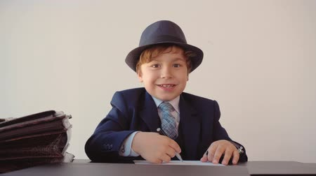 nákrčník : Child boy looks like a businessman is making paperwork in his office, puts his signature on the papers, closes the folder and puts the side of the paper. Adults life parody, front view.