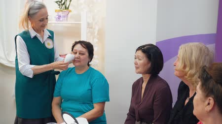 манипуляция : Senior grey-haired nurse woman demonstrates hardware facial massage against wrinkles on client to group of elderly women in clinic.