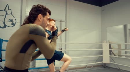 lutador : Professional training of two young fighters boxers making dynamic exercises in front of the mirror on ringside, boxing hands and kicking legs, side view. Stock Footage