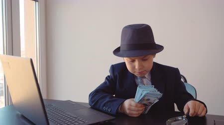 schoolkid : Portrait of child boy looks like a businessman in hat and suit is checking dollars with magnifier glass sitting at table near the laptop in his working office.