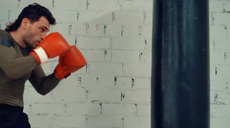 fight club : Boxer man in gloves training kick by boxing bag in sport club. Fitness man doing punches to combat bag on white brick wall background. Mixed martial arts. Fight training concept