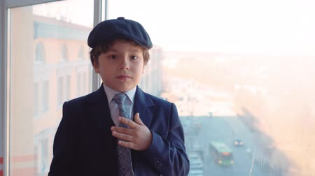 имитация : Portrait young boy in business suit straightens tie and cap on window background in office. Cute young boy correcting tie and looking to camera. Business kids concept