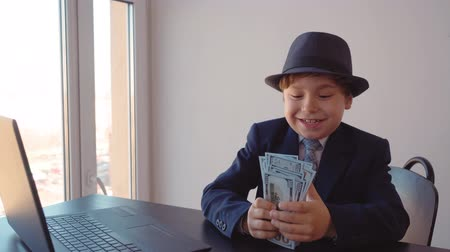 стремление : Happy young business boy holding in hands money stack sitting at table in business office. Rich entrepreneur holding money cash and enjoying wealth in work office. Successful business children concept Стоковые видеозаписи