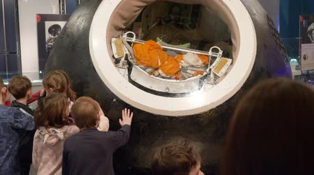 orbital : Moscow, Russia - March 21, 2019: capsule of Soviet spacecraft in astronautics museum. Children watching cosmic capsule while school excursion in space museum