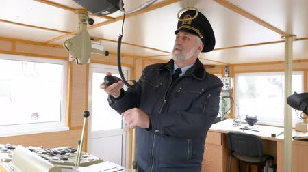 námořní loď : Elderly grey-haired captain in uniform on the boat in control room is setting radio communication and said on the transmitter.