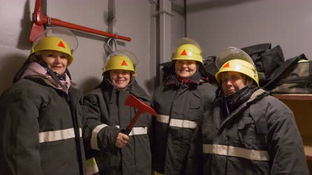heat resistant : Four woman firefighters in yellow helmets and uniform are looking in camera in smiling in fire station. Stock Footage