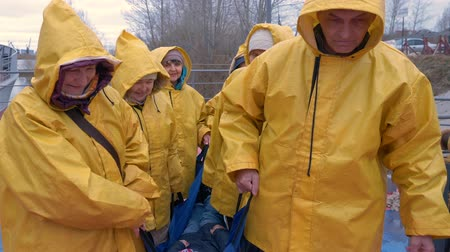 megmentő : Rescuers in waterproof yellow suits carry the victim all together on a stretcher. Professional rescue assistance in rainy weather. Stock mozgókép