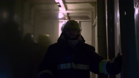 heat resistant : Professional fire team training. Women firefighters go through the tunnel in full uniform lighting the way with lantern. Stock Footage