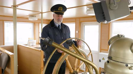моряк : Elderly grey-haired captain of the ship in peaked cap at the helm in the wheelhouse is talking about his job. Captain at the steering wheel of the ship
