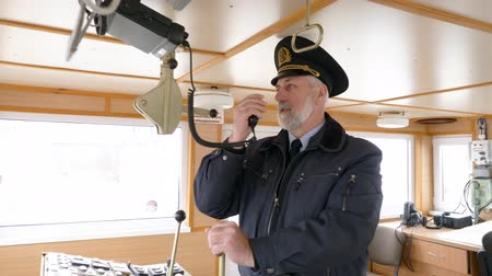 capitano : Bearded captain of ship setting radio on captain bridge. Navigation officer manage devices on navigation panel and dashboard in modern ship. Sailing and shipping concept Filmati Stock