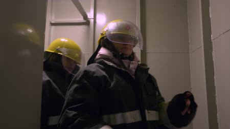 rescuer : Women rescuers in protective suits and helmets going in tunnel with hand flashlight while rescuing people inside building. Female rescuers team at dangerous scene Stock Footage