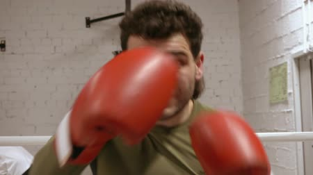 concentrando : Man professional boxer is doing boxing training to practicing hand punches in gloves in gym, kickboxing exercises. Slow motion front view fist hits