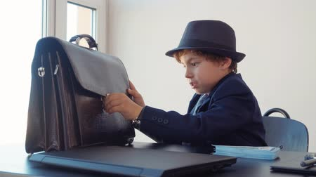 связать : Child boy looks like a boss is trying to open briefcase in his office sitting at table. Adults life parody, front view. Business man in hat. Banknotes on table desk Стоковые видеозаписи