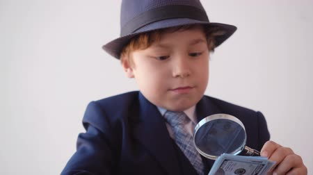 lupa : Portrait of child boy looks like a businessman in hat and suit is checking dollars banknotes with magnifier glass sitting in his working office.