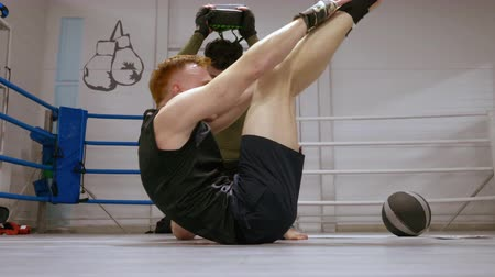 kulturystyka : Personal training of professional boxer making adominal exercise with his trainer laying on ringside and lifting his body and legs. Fighter hits partner to stomach of sparrer Wideo